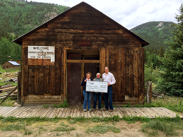 High Country Bank employees present a check to a member of the committee for the Historic St Elmo American House